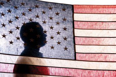 Juan Gilbert behind American flag