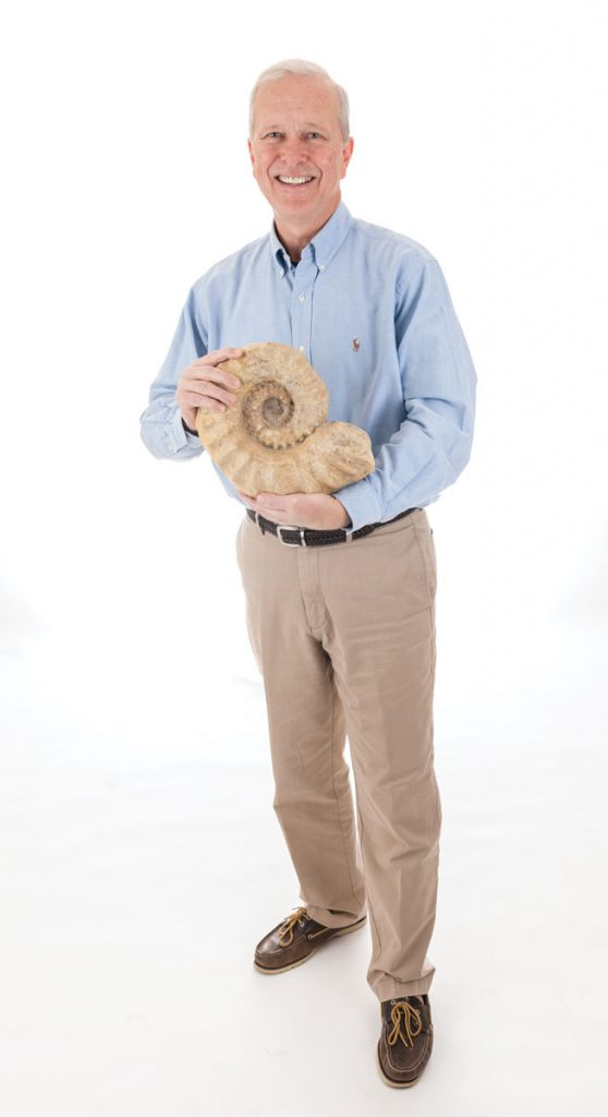 Doug Jones holds a Cretaceous-era ammonite, an ancient relative of the chambered nautilus that exists today. Photo Credits: Kristen Grace