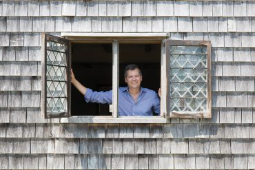 Marty Hylton peers out of a window in Nantucket's oldest house, the Jethro Coffin house, built in 1686.