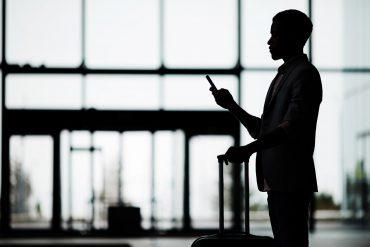 Man using phone inside airport.