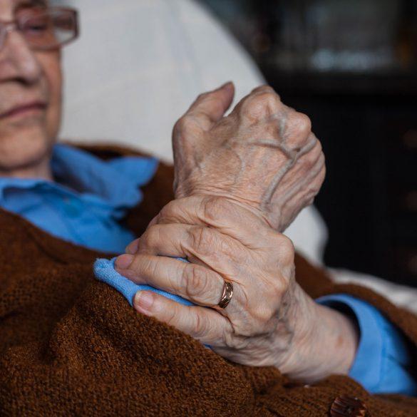 Senior citizen rubbing their wrist