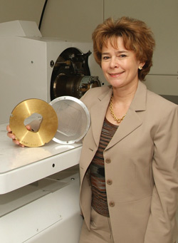 Dr. Nancy Mendenhall displays disks that direct the proton beam. The gold aperture has a two-dimensional window in the approximate shape of the target being treated. It blocks protons from traveling beyond the white acrylic compensator, which fine-tunes the beam's depth to an individual patient's treatment needs.