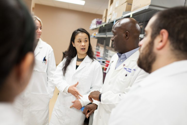 Dr. Jianping Huang (left center), Dr. Duane Mitchell (right center) and colleagues.