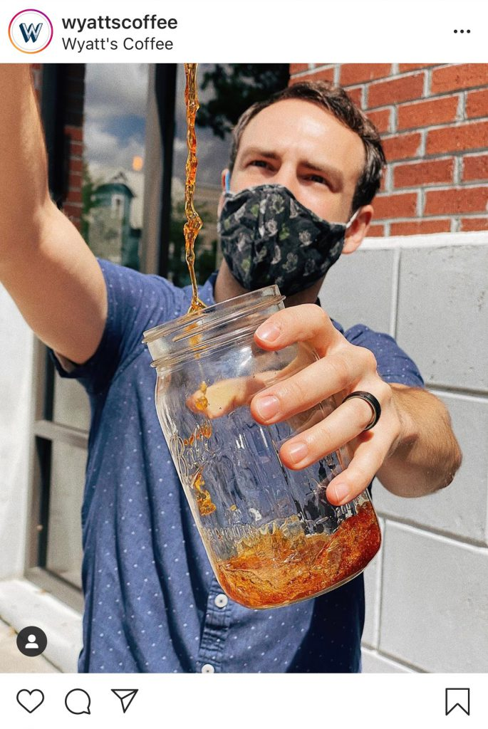 Wyatt's Coffee barista wearing mask and pouring coffee into mason jar