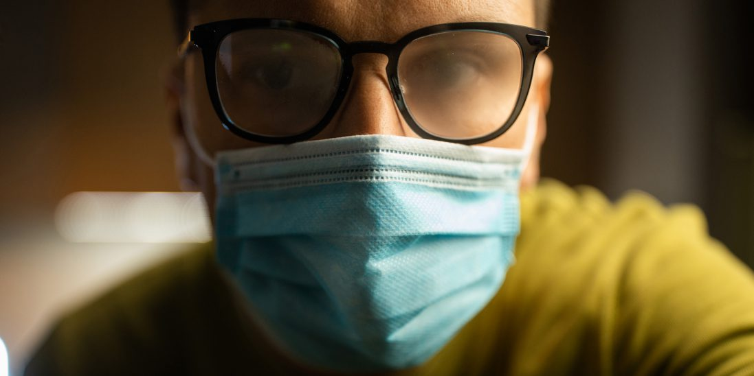 Person wearing protective mask and glasses with foggy lenses.