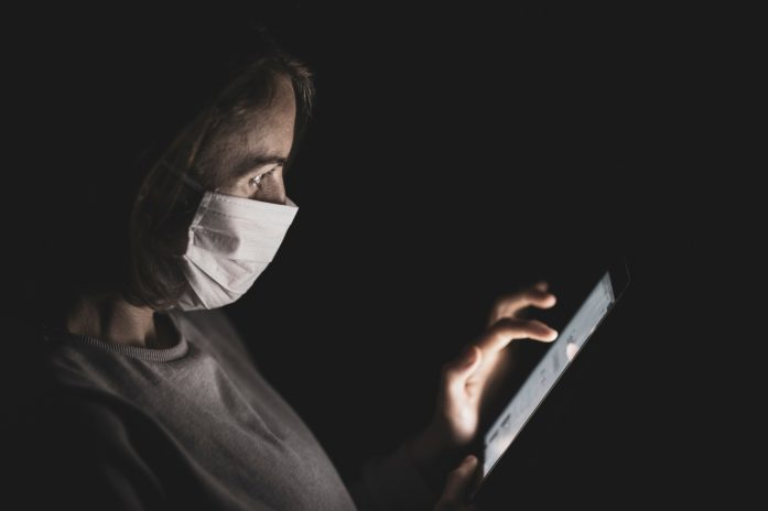 Woman wearing a protective mask while using a tablet.