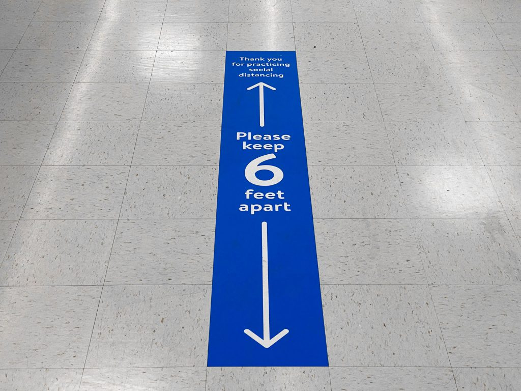 Decal stating social-distancing guidelines on aisle floor.