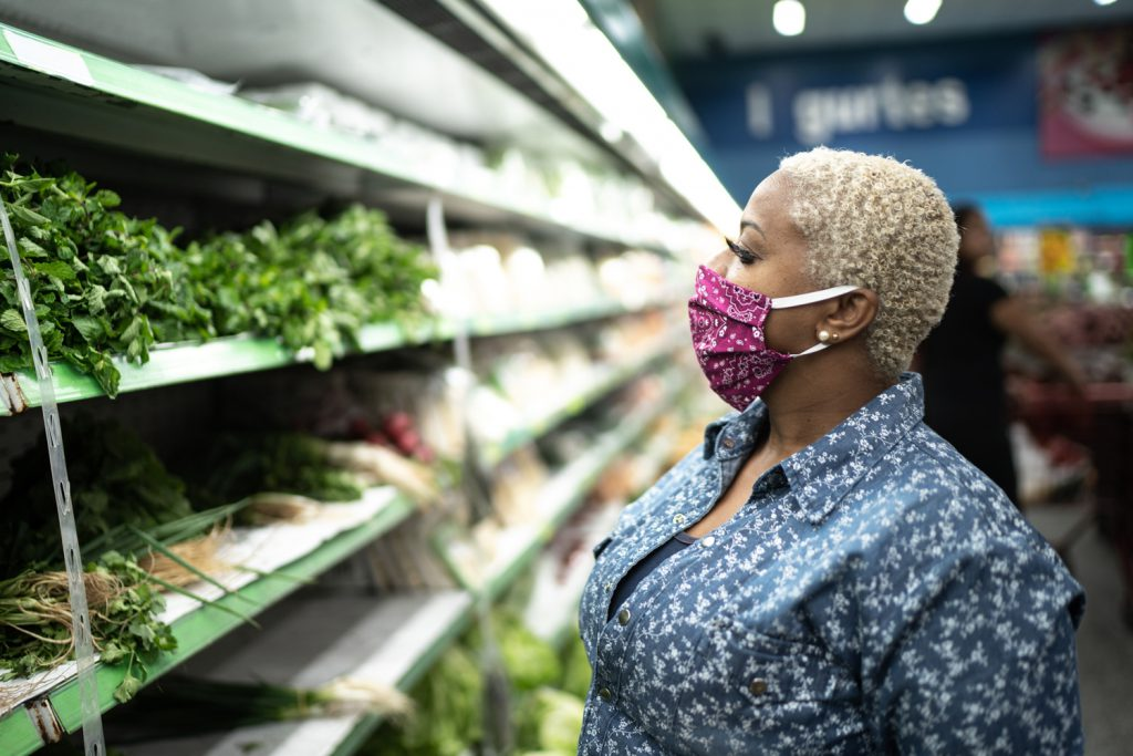 Woman looks at produce while wearing protective mask in grocery store.