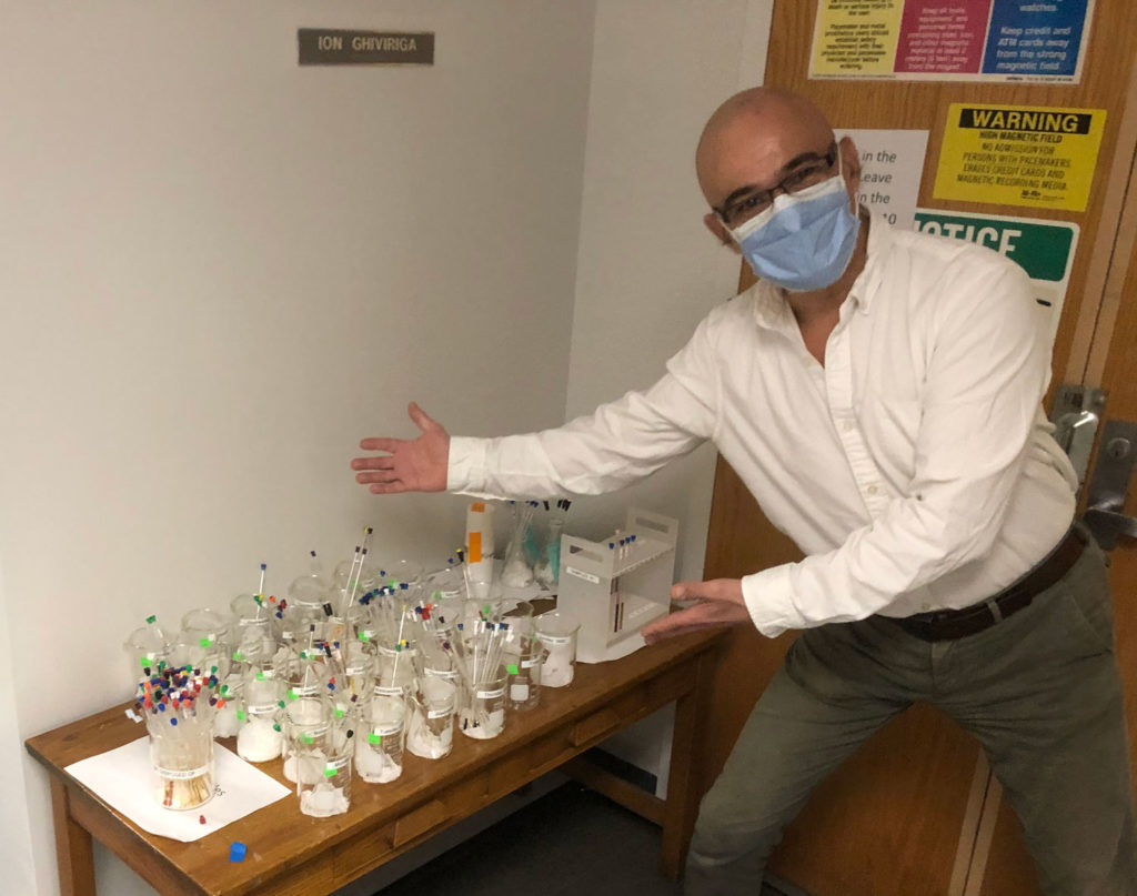 Ion Ghiviriga poses next to samples in his lab.