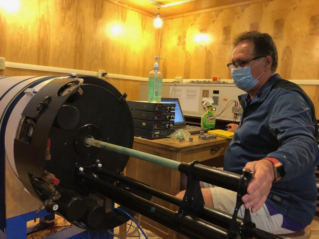 Joseph Meert wears mask while operating lab equipment.