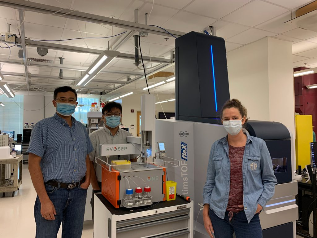 Biology Professor Sixue Chen, director of the proteomics facility, poses with Jin Koh, scientific director, and Bryndan Durham, after the unveiling of the new equipment.