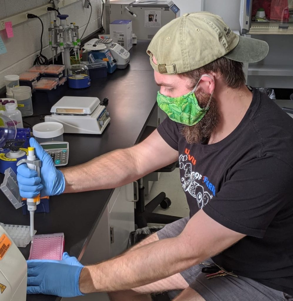 Arik Hartmann wears custom mask sewn by Ana Longo while working in research lab.